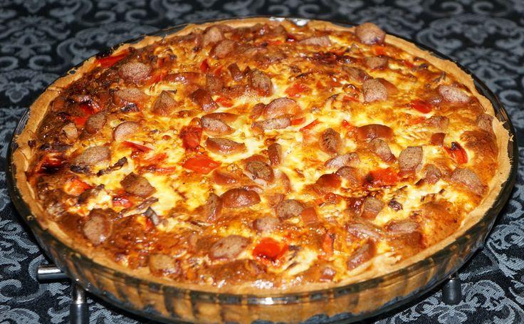 Skær pølserne i små tern og bland dem i en skål med de to slags ost.Beklæd en tærteform med tærtedejen og hæld pølseblandingen i formen.Pisk æg og mælk let sammen.Hak løget og peberfrugterne og bland dem i æggeblandingen.Krydr med salt og peber.Fordel æggeblandingen i tærteformen.Tærten bages ved 175 grader i en times tid indtil den er fast.Lad tærten hvile i 5 minutter inden servering. 350 g. pølser 80 g. revet emmentaler ost 65 g. revet cheddar ost 1 pk. tærtedej 6 æg 2½ dl. mælk 1 stort…