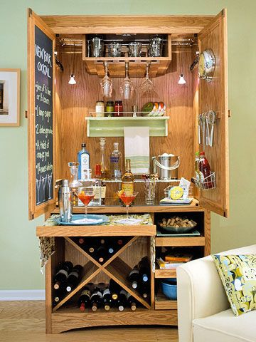 DIY Bar from old armoire: Stemware, wine,& mixers  in stained and modified armoire. When it's time to create the concoctions, just pull out the wide shelf for a roomy mixing surface. Close at hand, a door is transformed into a convenient recipe center with the simple addition of chalkboard paint. Show off your cellar by removing the armoire's bottom doors. Buy a ready-made wine rack or create dividers such as these from veneered plywood.