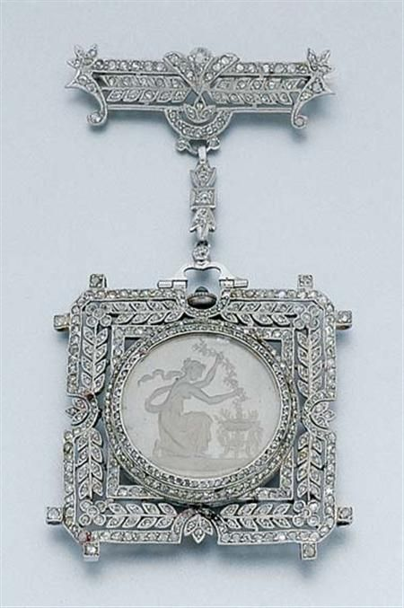 Diamond and Rock Crystal Intaglio Lapel Watch   Platinum, centering a circular rock crystal intaglio depicting a Grecian woman gathering a garland from an urn, within a square-shaped plaque designed with an intricate garland motif, joined by a diamond-set bow, topped by a pierced diamond-set bar brooch, of similar garland design, set throughout with numerous rose-cut diamonds, Swiss movement, circa 1910, approximately 17.4 dwt gro