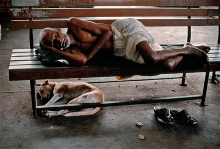 railway porter sleeping in train station as he waits for train to arrive, India. Photo by Steve McCurry