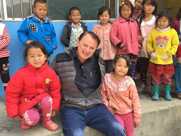 Phillip Oney with the two girls he sponsors at Lin Wang School