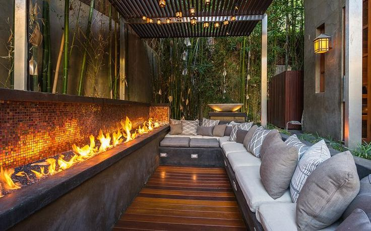 Asian style patio features a concrete L shaped built in sofa lined with white and gray cushions facing a long concrete fire pit accented with a mosaic tiled backsplash tucked under a black pergola surrounded by bamboo trees.