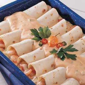 Creamy Seafood Enchiladas Recipe -Shrimp and crab plus a flavorful sauce make these enchiladas outstanding.  I made them for an annual fundraiser, and now they're always in demand. Spice up the recipe to your taste by adding more green chilies and salsa. —Evelyn Gebhardt, Kasilof, Alaska