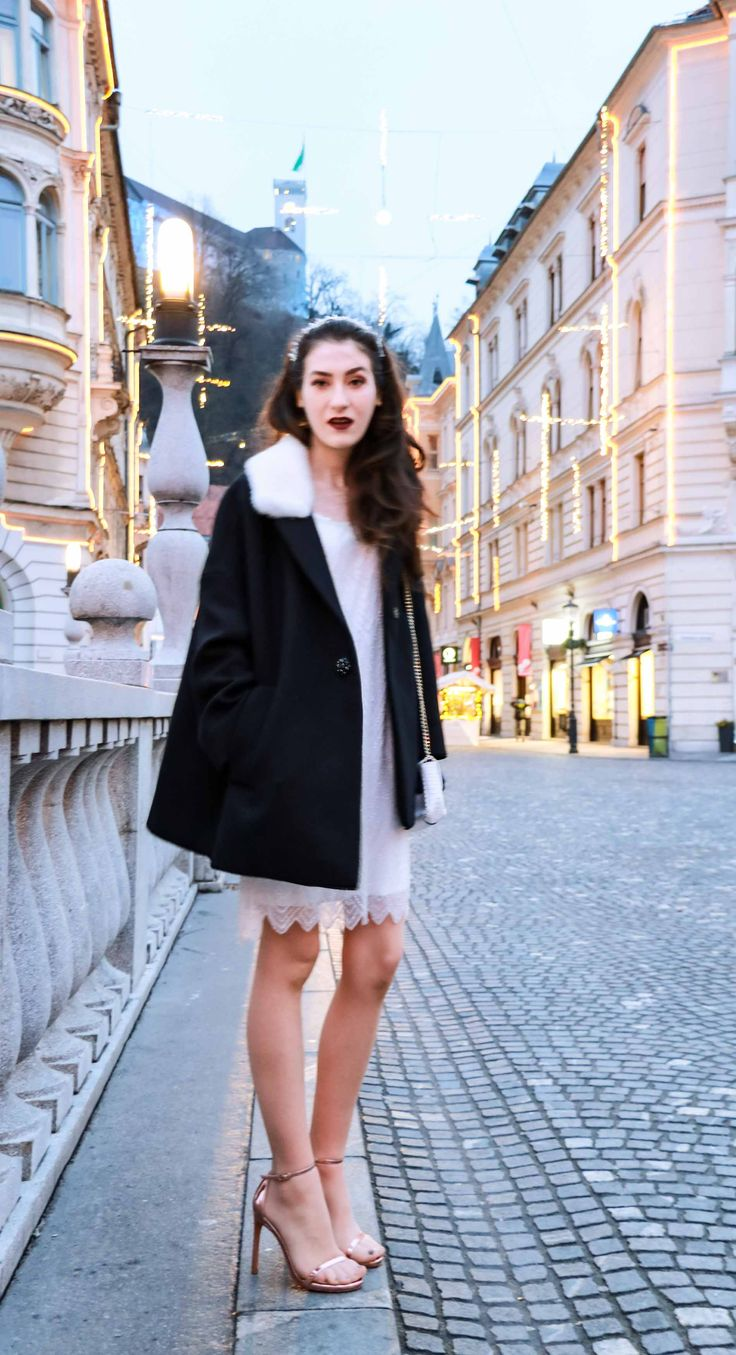 Fashion Blogger Veronika Lipar of Brunette from Wall Street dressed in white sequinned dress, short loose black and white coat from Escada, rose gold metallic in high-shine glass sandals from Stuart Weitzman, blue glove, and wearing white shoulder bag and tiara for New Year's Eve Party