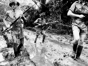 Milne Bay: Australian Troops plough through mud at Milne Bay shortly after the unsuccessful Japanese invasion attempt. (AWM 013335)