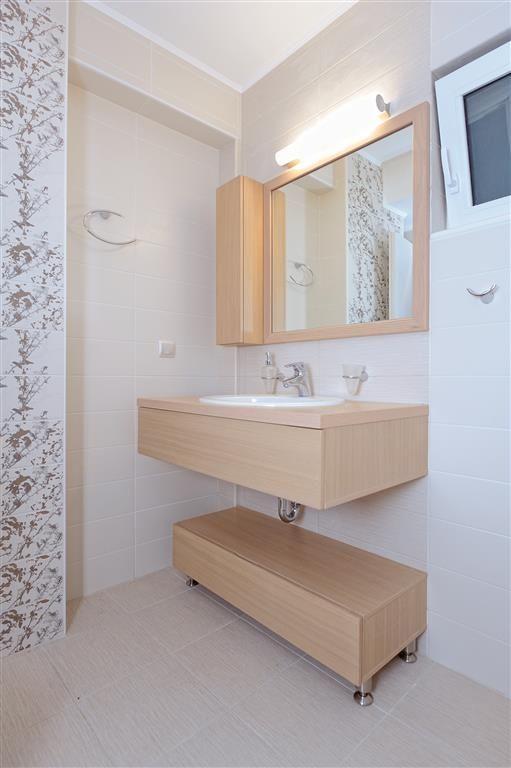 Έπιπλο μπάνιου από φυσικό δρυ με καθρέπτη, κρεμαστό ντουλάπι και μεταλλικά πόδια στη βάση.