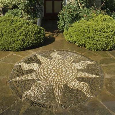 """A cheery sun mosaic set close to an entryway is a great way to say """"welcome to our home."""" Although sun motifs are common in outdoor décor, this oversized version is impressive in its intricacy, and makes a bold statement that your guests will remember for a long time."""