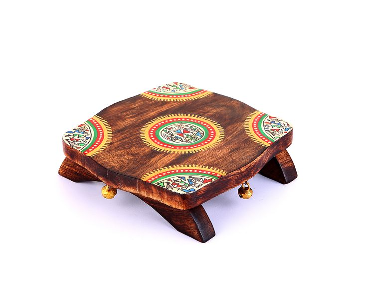 Multi purpose chawki made from Mango wood. Beautifully handpainted with Warli design. Adorned with ghunguroos on all four sides. Can also be used on your dining table as a dish coaster. (Shipped without the idol).