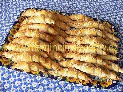 Sýrové česnekové rohlíčky  těsto: 500 g polohrubé mouky, 200 g Hery, 100 g strouhaného sýra, 1 kostička droždí (42 g), lžička soli, 1 vejce, 100 ml mléka náplň: 1 palička česneku (klidně i víc), špetka soli 1 vejce na potření
