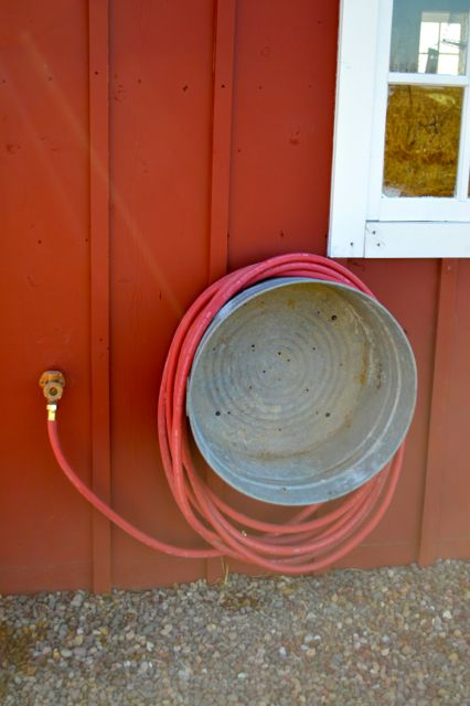 A vintage wash basin affixed to the side of this barn adds a pretty touch and practical solution for storing the garden hose. | Via newlywoodwards.com