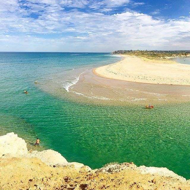 Onkaparinga river mouth in South Australia. The beach here is called Port Noarlunga, and the reef that shelters it from large waves makes for ideal swimming conditions. Surf lifesavers are on patrol over the summer months, and the area is surrounded by picturesque steep red sandstone cliffs, which is typical of South Australian beaches.