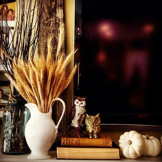 Layer your mantel with harvest decor like wheat, branches, and pumpkins. Using a water pitcher is a great substitute for a vase.  Source: Instagram user vintagegrey