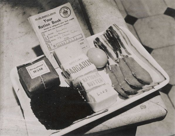 Beside a ration book are one persons rations for a week - including four rashers of bacon and one egg.