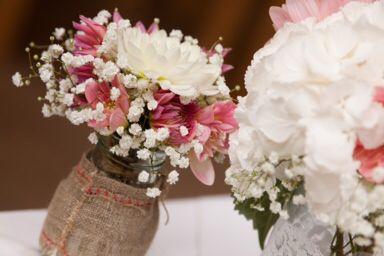 Rustic jam jars with gypsophila and dahlias. Wedding table flowers