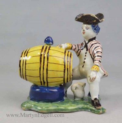 Polychrome Delft sitting man with barrel and jug