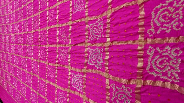ascinating Fuchsia - Bandhani Dupatta Gharchola style dupatta will all over zari checks and very fine yellow and white small bandhej dots. Beautiful Bandhej patterns made out of traditional handicraft tie n dye technique. Lagdi patto (Broad zari) pattern at both the ends escalates the beauty of fuchsia color.   www.sankalpbadhej.com  For more details/collaboration call/whatsapp - 9377399299 #sankalpthebandhej #bandhanidupatta #gharchola #dupatta #bandhej #tiendye #pinkdupatta