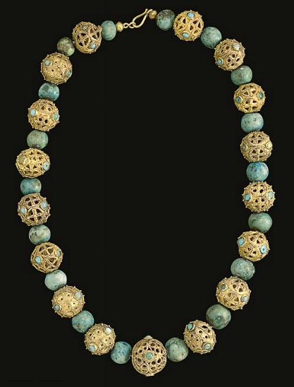 A Middle Byzantine or Islamic Gold Bead Necklace, ca. 8th-9th Century A.D.; 17 beads composed of gold sheet cut out to form openwork designs embellished by filigree and granulation, some with circles with cruciform motifs and some with circles within circles, round and oval bezels vertically between, now set with turquoise and blue glass, interspersed with turquoise beads; strung with a modern hook-and-loop closure 24¾ in. (62.9 cm.) long