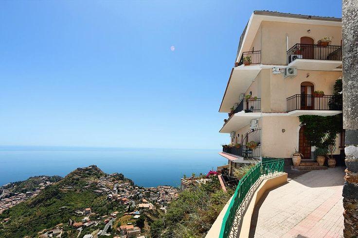 Description: Gezellig hotel aan het mooie plein met een van de prachtigste uitzichten van Sicilië  Wat een uitzicht! Boven Taormina met een van de mooiste uitzichten van Sicilië ligt Castelmola een middeleeuws stadje gebouwd op 3 heuvels. Wanneer je naar het oude Castelo Normanno loopt zie je aan de ene kant Taormina onder je liggen met daarachter de zee en het vasteland van Italië. Als je je omdraait heb je een prachtig uitzicht op de Etna. Veel mooier kan het niet.  Wat een bijzondere…