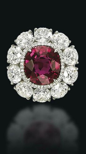 An exceptional ruby and diamond ring set with a cushion-shaped ruby, weighing approximately 6.25 carats, in a micro-pavé diamond surround, to the brilliant-cut diamond cluster, mounted in platinum, ring size 5¾ Accompanied by report no. CS 58693 dated 13 November 2014 from the AGL American Gemological Laboratories stating that the ruby is of Burmese origin, with no indications of heating, and a Jewel Folio mentioning the outstanding quality of the 'Pride of Burma'.
