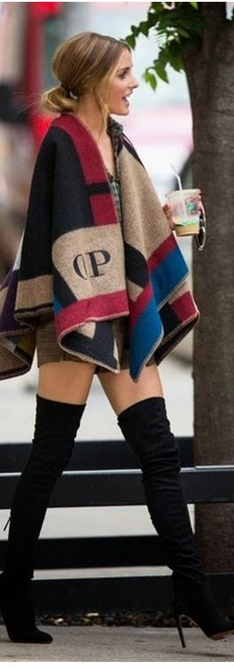 Olivia Palermo in Burberry Fall 2014 red print poncho sweater and Stuart Weitzman black thigh high boots.