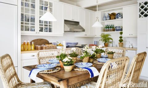 In the kitchen, a custom Holland & Company farm table doubles as a dining and work surface. Wicker chairs from Mainly Baskets (with cushions in a Cowtan & Tout fabric) help to visually connect the room to the adjacent backyard, enabling the space to feel more expansive than its square footage might suggest. For a cohesive look, appliances are paneled to match the cabinetry, which is painted in Benjamin Moore's White Dove.