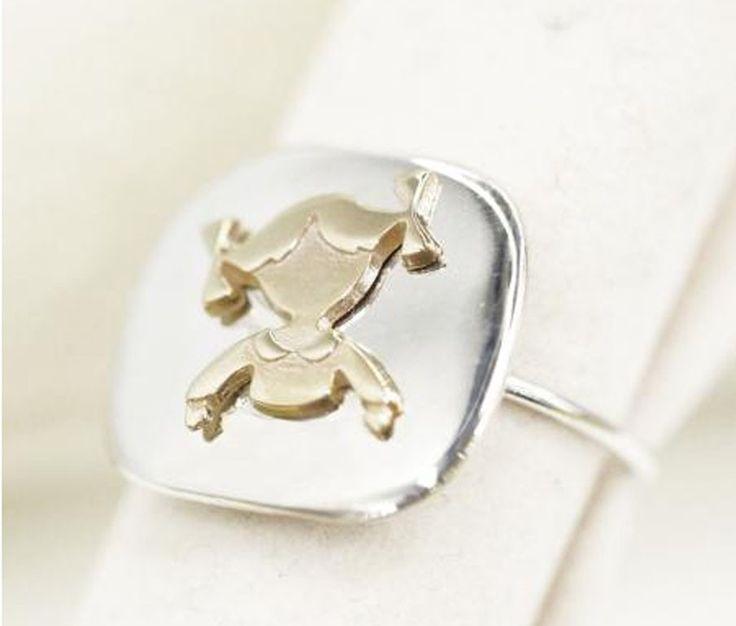 Anello regolabile in argento rodiato con sagoma bimba in oro giallo.