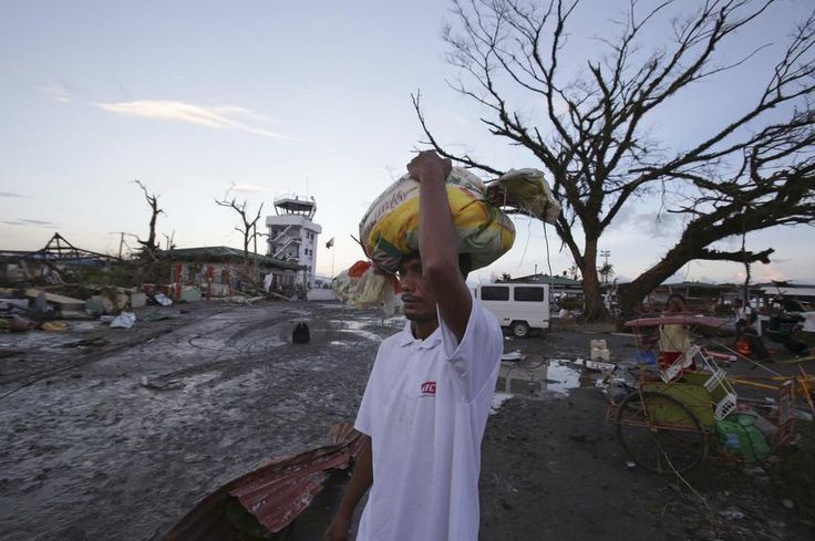 Nov. 2013: A survivor of Typhoon Haiyan carries relief goods and looks upon the destruction, Tacloban, the Philippines. - Found via Buzzfeed