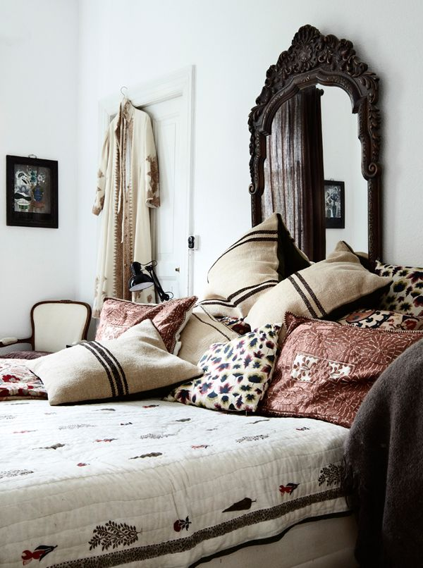 Like the mix of bed linens and the mirror that is acting as a headboard