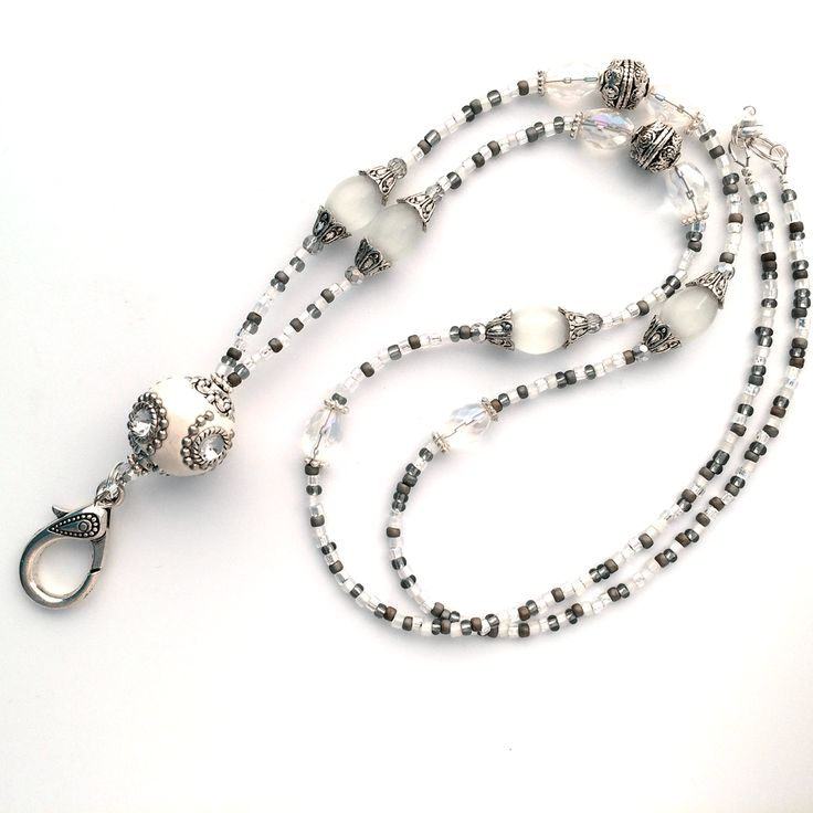 This white and silver beaded lanyard features a large white Indonesia bead as the focal point. Other white beads and decorative silver beads and bead caps are added to the design. Small silver gray gl