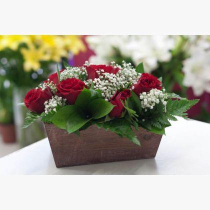 Σύνθεση με κόκκινα τριαντάφυλλα σε ξύλινη θήκη.