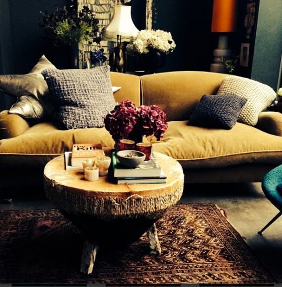 mustard yellow velvet sofa and African drum table + red and teal accents (Abigail Ahern)