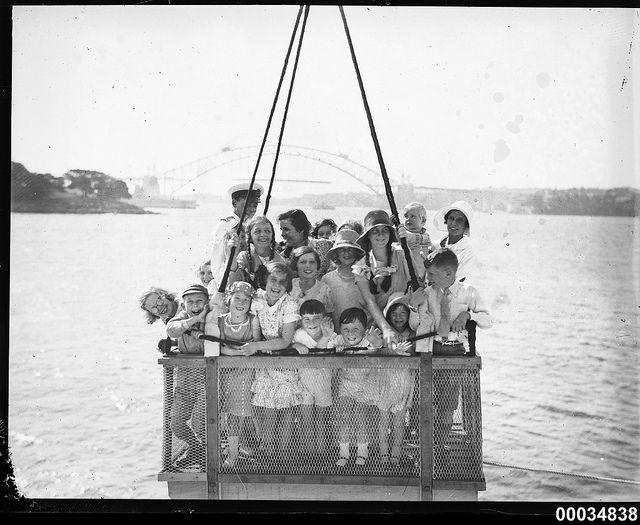A group of children hoisted by a crane on board HMAS AUSTRALIA II, December 1930