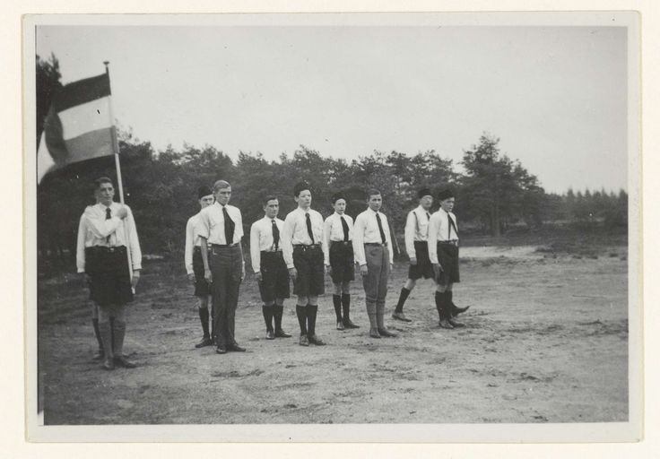 NSB | Jongens van de Jeugdstorm met de Nederlandse vlag, NSB, Anonymous, 1934 - 1935 | Jongens van de Jeugdstorm tijdens of na het afleggen van de gelofte op de Jeugdstorm tijdens hun installatie als lid. Links een lid met de Nederlandse vlag. Op achterzijde foto: Installatie van troep I. ( Gelofte ). De foto maakt deel uit van een serie van circa 35 amateurfoto's.