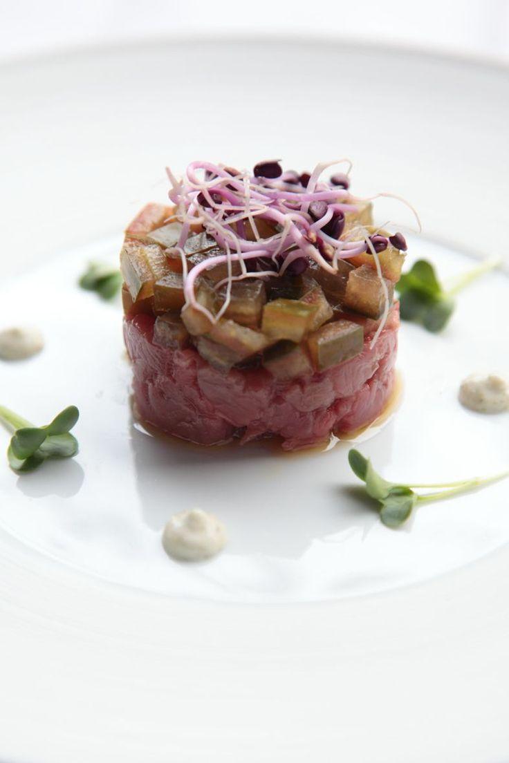 Bereiden:Hak de tonijn fijn met een koksmes. Meng met piment, peper en zout, peterselie en olijfolie.Snijd de tomaat in 4, haal de zaadjes eruit. Snijd in kleine blokjes, kruid met peper en zout.Meng de mayonaise met de wasabi, plattekaas en wat limoensap.Doe in een spuitzak.Zet een dresseerring midden op het bord, vul die tot de helft met tonijntartaar. Vul aan met tomaat. Druk lichtjes aan, neem de ring voorzichtig weg. Werk af met enkele toefjes wasabi mayonaise.