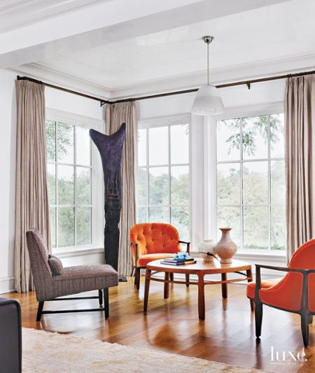In Its Contemporary Living Room Two Orange Velvet Chairs Pull In The Faded  Hues Of The Adjacent Oushak Rug.