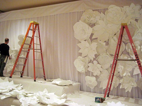A wall of paper flowers being created