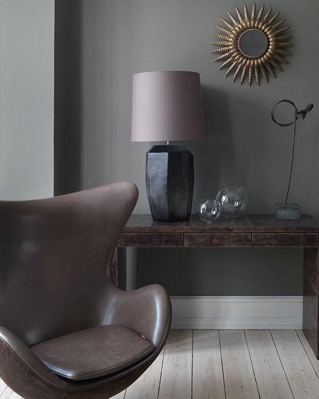 Brunlige nuancer fra læderet på Arne Jacobsens Ægget og læderkonsolbordet fra Rue Verte blandes smukt med kølig grå fra vægfarven og en Guaxs-glaslampe fra Rue Verte  Foto: Mads Mogensen. Af: Martina Hunglinger. #arnejacobsen #ægget #stue #lampe #bobedre