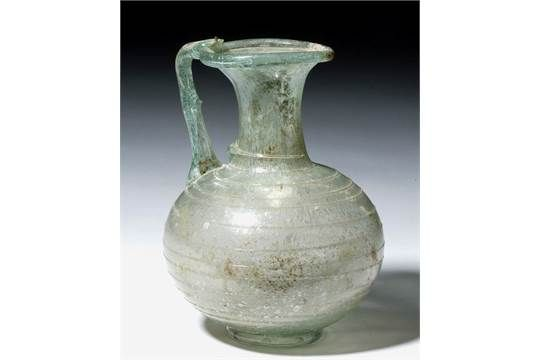 """Roman Empire, eastern Mediterranean, ca. 1st to 3rd centuries CE.After the invention of blown glass in the first century CE, glass became easy to mass produce as well as cheaper, and so glass items entered everyday Roman life for the majority of householders; a small vessel like this one may have been used for pouring olive oil. Size: 5"""" H (12.7 cm)"""