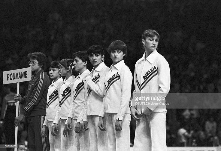 World Championships Of Artistic Gymnastics From 1978 To Strasbourg. A Strasbourg, en 1978, lors des XIXèmes championnats du monde de gymnastique artistique, l'équipe des gymnastes roumaines, posant alignées, en tenues aux couleurs de leur pays, avec leur entraîneur portant une pancarte au nom du pays, de gauche à droite, une personne non-identifiée, Emila EBERLE, une personne non-identifiée, Teodora UNGUREANU, Nadia COMANECI et une personne non-identifiée.