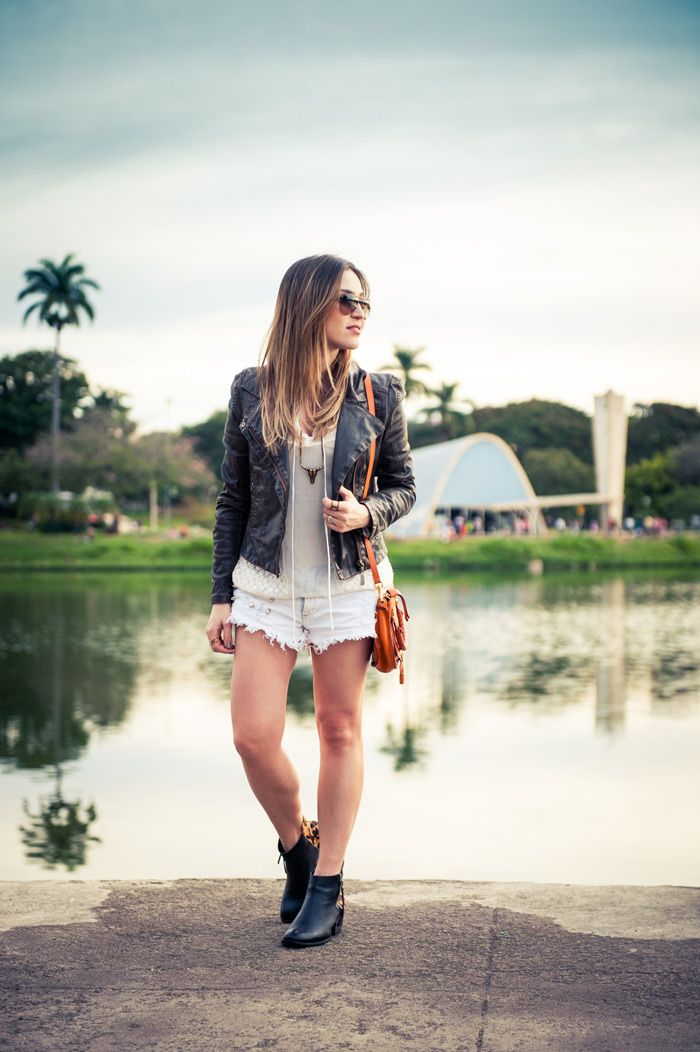 Lu Ferreira, BH. Look com shorts branco jeans, botinha e jaqueta de couro, com bolsa laranja para trazer uma pitada de cor.
