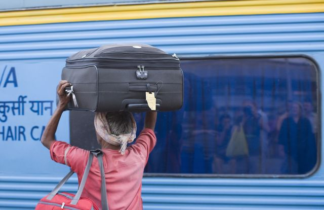 Read These Tips to Find and Board Your Indian Railways Train: A porter carries luggage on Indian Railways.