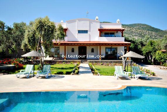 Bodrum Bitez'de bulunan bu 4 yatak odalı ve özel havuzlu villa, etrafı duvarla çevrili geniş bir bahçeye sahiptir. Gözlerden uzak ve huzurlu bir tatil arayan aileler için idealdir.