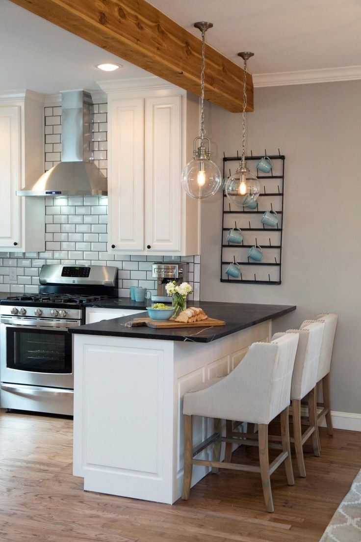 Fixer Upper hosts Chip and Joanna Gaines installed a natural wood support beam above the breakfast bar. All new white cabinets and black marble countertops bring a modern look to the kitchen, and two hanging globe light fixtures illuminate the breakfast bar. A new stainless steel range and vent hood is surrounded by a beveled subway tile backsplash to complete the stylish look.