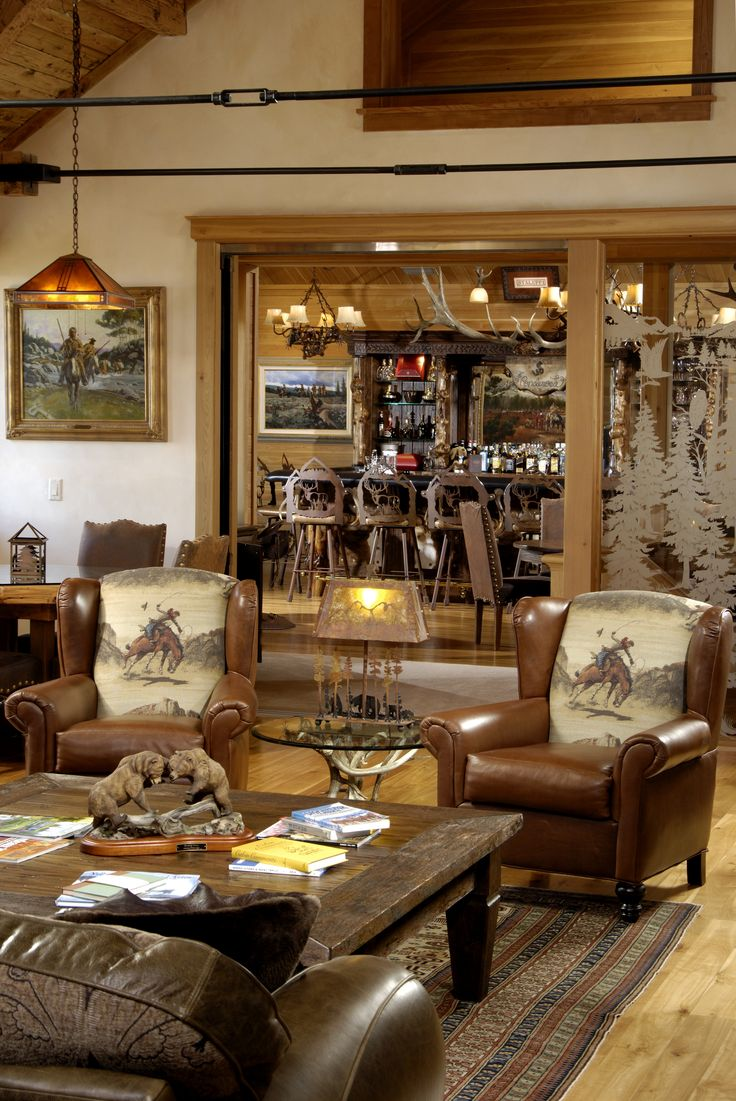 Rustic western ranch home... love the cowboy chairs and the antler chandeliers.
