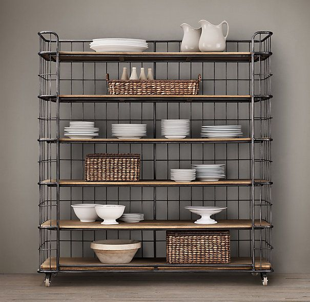 A rolling baker's rack from the early 20th century, a time when commercial bakeries let their products rise, rest and cool on movable racks exactly like this. Its C-shaped frame was designed to help keep contents in place, now it would make a great place for plates