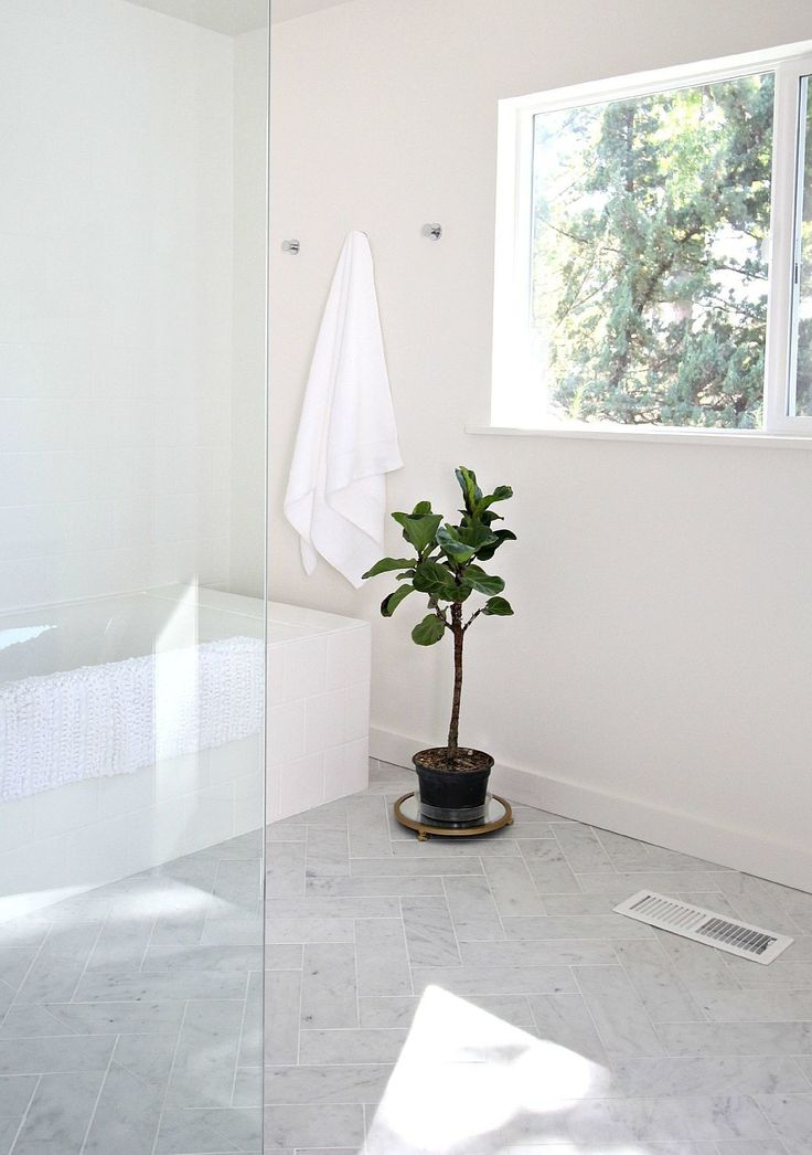 When soaking in a bathtub, being able to stare out a beautiful window adds to the picture-perfect scene. I always suggest adding natural light to bathrooms. Windows bring the outdoors in, and if you have a fantastic view, enjoy it from your tub. A classic yet trendy option for flooring is herringbone. We created the pattern in marble with white grout. It's the perfect complement for this space. The tiling around the tub and two main walls are square white tiles with white grout.