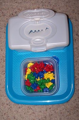 Placing toys into empty wipe container ...