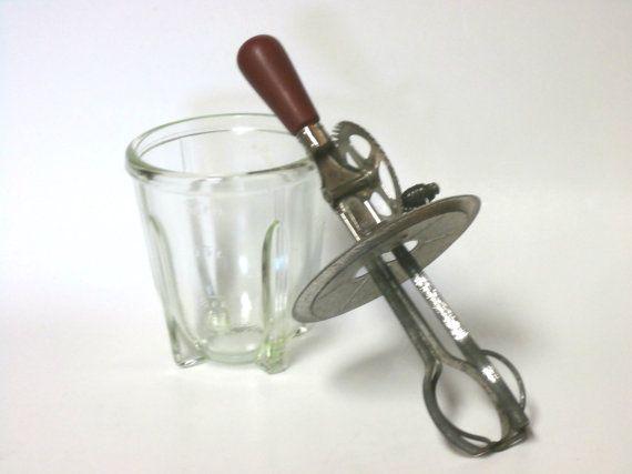 Antiquariato A & J 1923 frullino per le uova con bicchiere misurino. Battitore ha un manico di legno che è dipinto in rosso, e non non cè nessuna perdita di vernice. Vetro tiene fino a 3 tazze con misurazione marchi-tazze, pinte e ournces. Il vetro non ha nessun chip, crepe o graffi. La frusta di metallo ha pochissima ruggine, ed è funzionante. laltezza totale è 11 1/2 alto, e il vaso di vetro si è circa 5 1/2 alto.    * Ordini internazionali, si prega di convo me per un preventivo di…