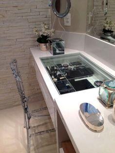 Na continuação do tampo do lavatório, a arquiteta Selma de Sá criou esta penteadeira prática com tampo de vidro e gavetas com organizadores. Além do espelho do banheiro, um outro menor, de aumento e com iluminação independente, ajuda na hora da maquiagem