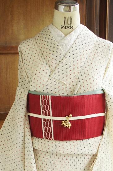 生成り色の地に、赤と青でボーダー状に色分けされた星のような十字絣が織り出された麻の夏着物です。